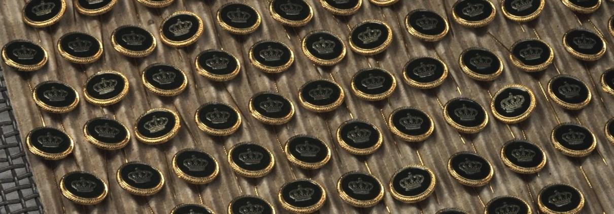 Manufakturen-Blog: Die Anstecknadeln sind geprägt, geschliffen und poliert - jetzt wird das Emblem farblich abgesetzt und die Farbe eingebrannt (Foto: Wigmar Bressel)