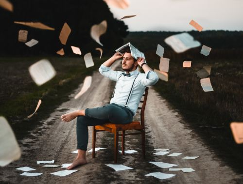 a man sat on a chair holding an opened book above his head like an umbrella from falling PIP papers