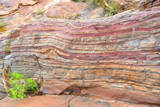 Banded iron formations Karijini National Park, Western Australia. The layers of reddish iron show the presence of oxygen, which bonded with the iron to form a rust-like iron oxide. These formations date most commonly from the period of 2.4 to 1.9 billion years ago, after the Great Oxidation Event.