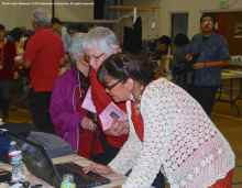 Manzanar Committee's Vicky Perez-Geaga (at computer) helps someone to sign an online petition opposing the construction of a 1,200-acre solar generating station adjacent to Manzanar.