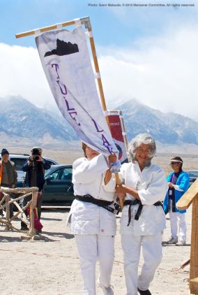 Banners representing all of the American concentration camps during World War II, the Crystal City Internment Camp, and a banner honoring the 100th Battalion/442nd Regimental Combat Team/Military Intelligence Service, are part of each year's Manzanar Pilgrimage. Carrying the Tule Lake banner is Nancy Oda (left, obscured) and Ernie Jane Nishi (right).