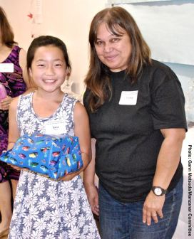 Sara Omura (left) with her second raffle prize win of the day, shown here with Manzanar Committee member Vicky Perez