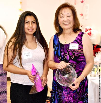 Emely Martinez (left) with her raffle prize, shown here with Manzanar Committee member Kerry Cababa