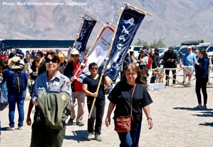 Banners representing the 10 American concentration camps, the Crystal City Internment Camp, and the 442nd/100th/MIS during a processional to the Manzanar cemetery