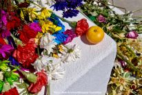 Flowers and what appears to be a persimmon or a tomato left at the cemetery as an offering during the interfaith ceremony
