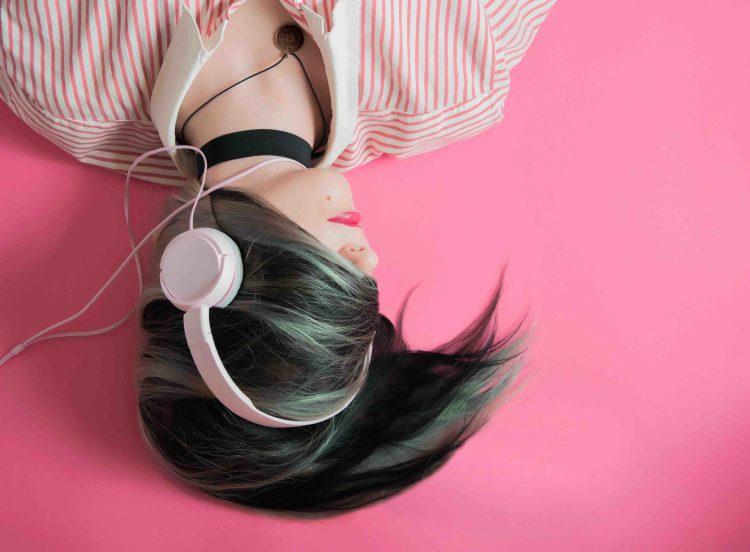 Fille tête en bas écoutant de la musique avec un casque blanc.