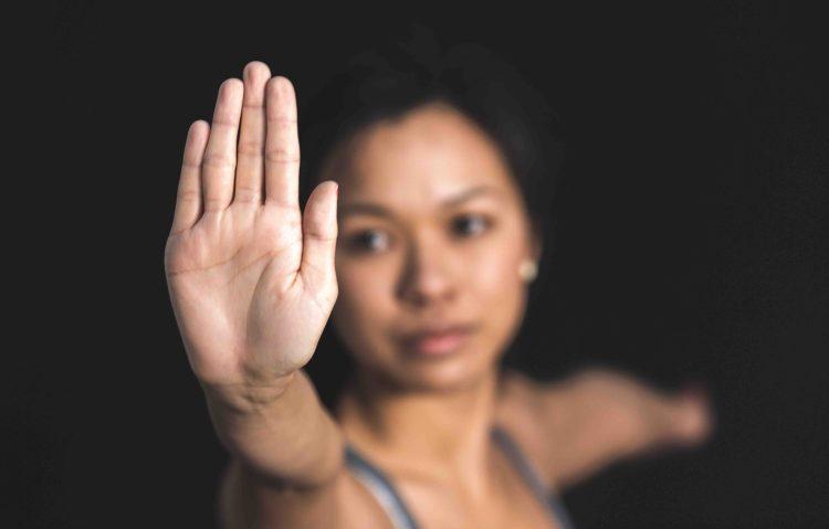 10 bonnes raisons de renoncer à vous battre : femme faisant du yoga et disant STOP avec la main