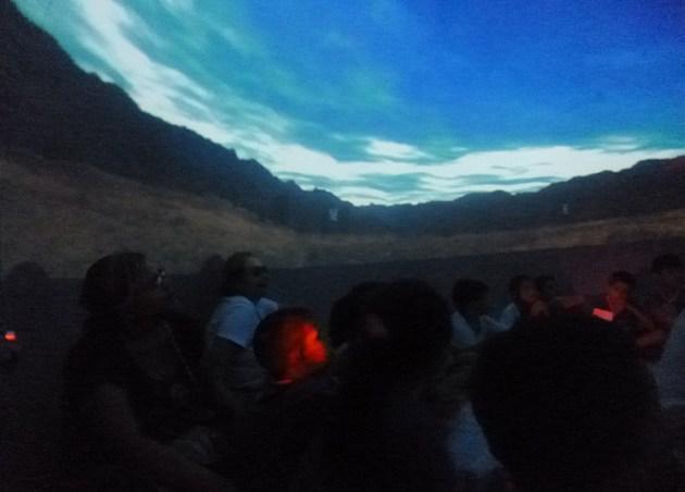 Alunos e professores sentados enquanto uma projeção mostrando o céu aparece à sua volta.