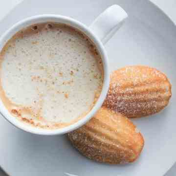 eggnog madeleines on plate with a latte