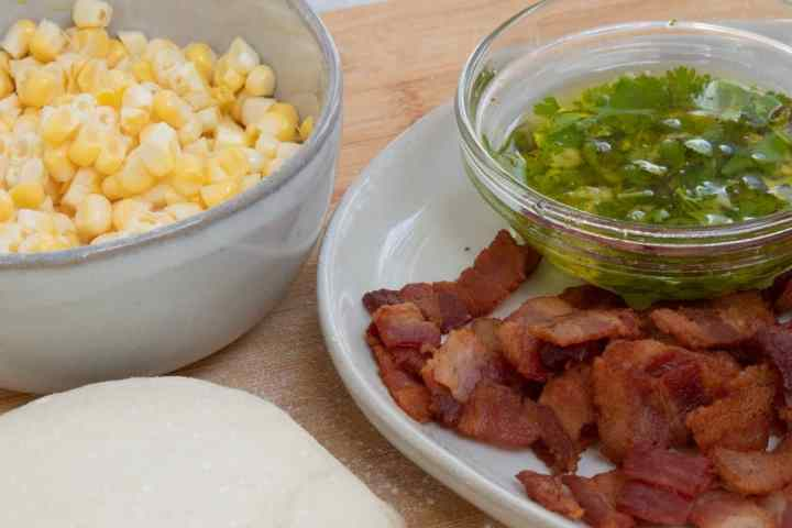 sweet corn, bacon, olive oil and pizza dough on a cutting board