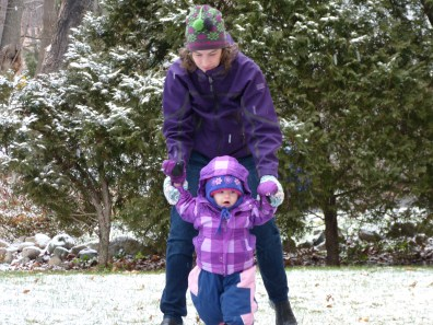 Mom helps Audrey waddle in her poofy snow pants