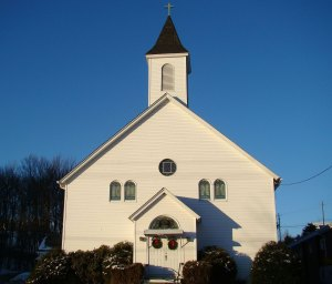A white church building with Christmas wreaths on the doos