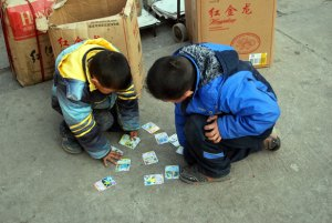 Two young boys trading baseball cards