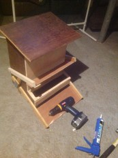 Feeder with the step lever weighted down with the screw driver and the food bin now uncovered