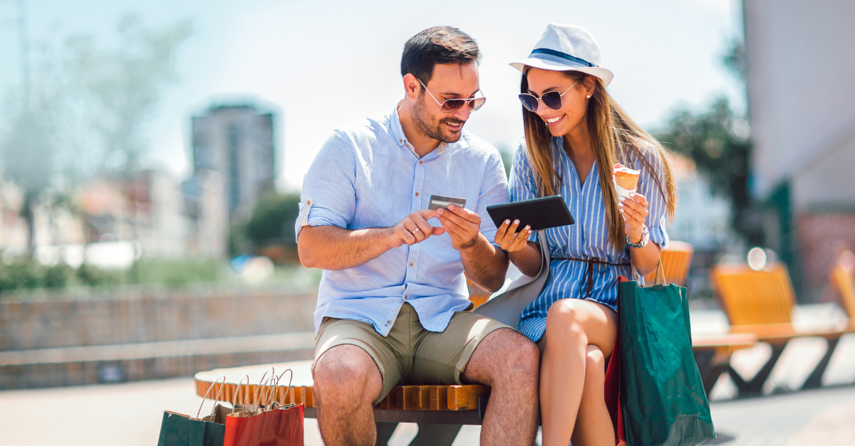 Couple sitting on outside bench with shopping bags while shopping online
