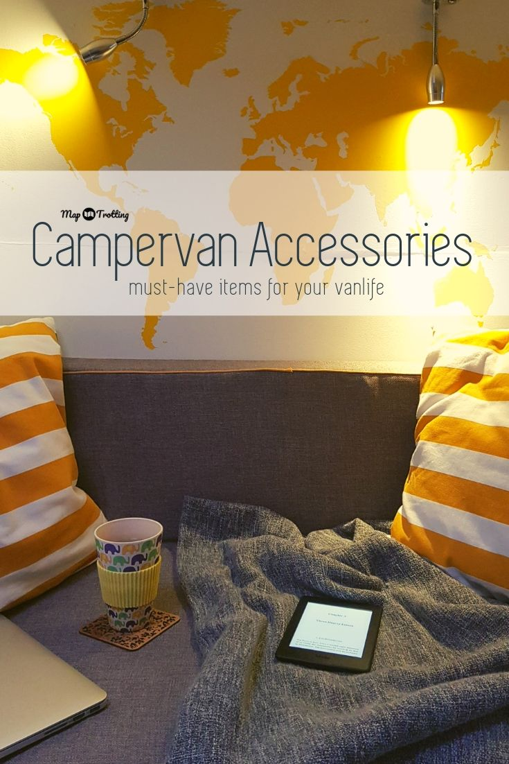 A cosy evening scene achieved inside a van with the campervan accessories such as a vinyl yellow world map lit up with two lights, two stripy pillows, bamboo mug, Kindle reader, MacBook and a throw.