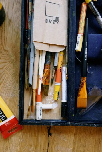 artist case with assorted paint brushes on wood