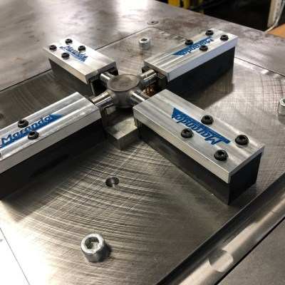 """Four 3D printed tooling blocks with """"Marando Industries"""" in blue on top of the metal. They are on top of a greaser table and have tubes coming out of the tooling that feed grease into a part that goes in the middle of the four 3D printed tools."""