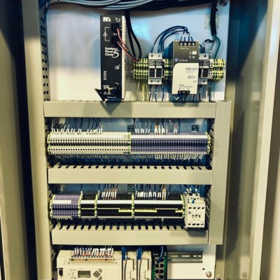 The wiring of a control system inside a panel box. The wiring is neatly organized and the control system is dense.