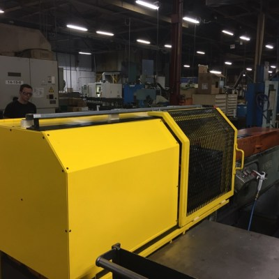 A yellow metal safety guarding system is encasing a machine. It is solid on half of it but the other half you can see through the panelling to see what the machine is doing.