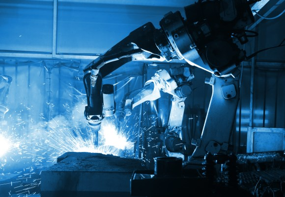 A robotic welding cell in action with sparks flying out of it. The lighting of the image is blue.