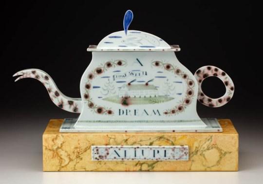 """Mara Superior, """"Allure, A Dream House"""", 1996, 15.5 x 22 x 7"""", high-fired porcelain, ceramic oxides, underglaze, glaze, faux marble paint, wood, brass pins. Bennington Museum of Art (2019.1.3.a-c)."""