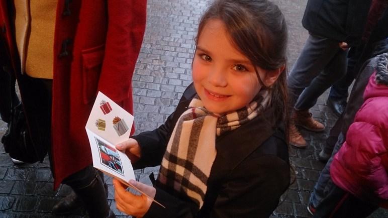Petite fille avec une carte souvenir du Père Noël sur le marché de noël de Nantes