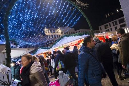 Nombreux passants sous les arches lumineuses du marché de noël de Rouen