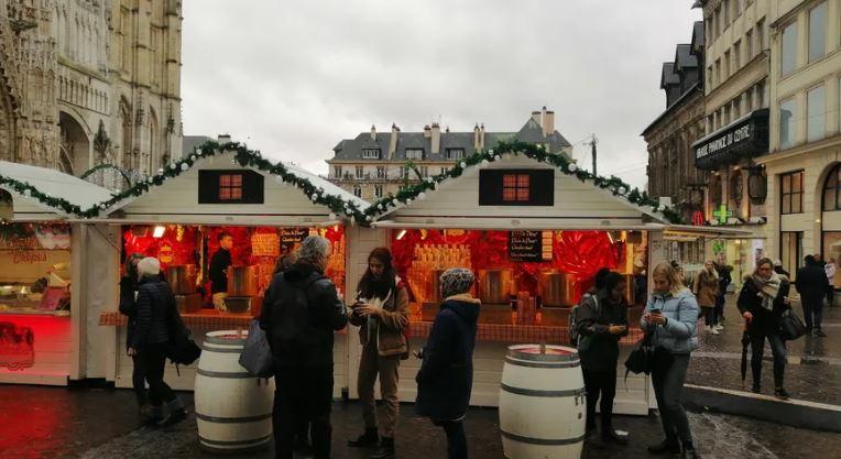 Les visiteurs du marchés de noël se réunissent devant un verre de vin chaud
