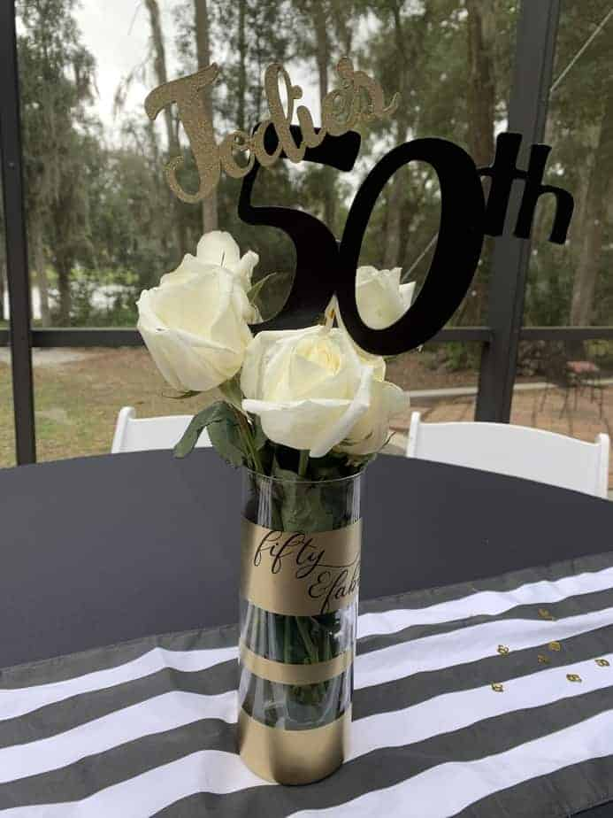 vase with white roses and 50th birthday sign