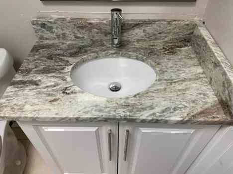 Updated bathroom with granite counters in condo flipping project