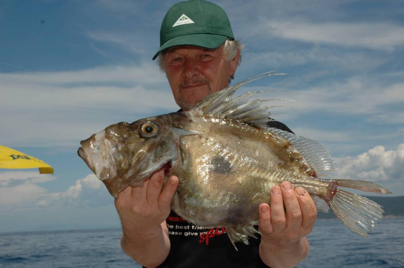 Il pescatore mostra con orgoglio la propria preda