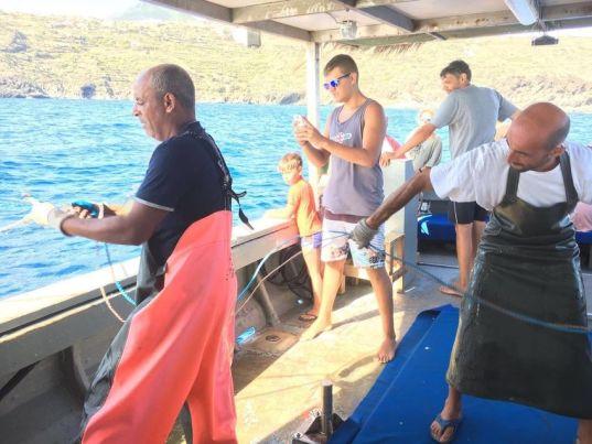 Turisti che assistono all'azione di pesca di una barca adibita a pescaturismo