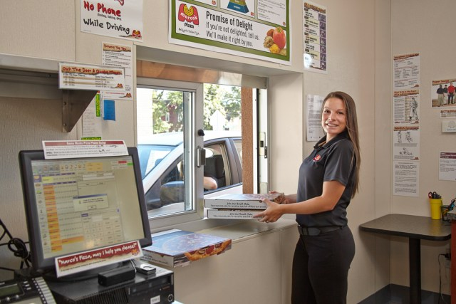 A franchisee smiles while handing two pizza boxes to a customer through the drive-thru window at her location.