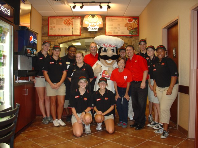 The team at a Marco's franchise location poses with a Chef Marco® mascot in front of the counter and menu boards.