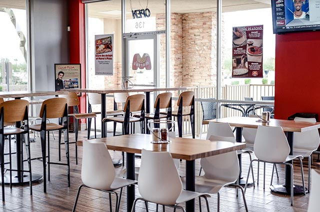 The interior of a new Marco's Pizza store; the camera looks out over tables, chairs and the front door.