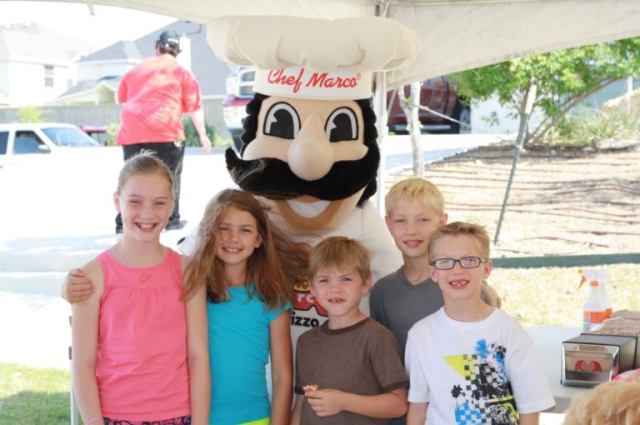 Five smiling children pose with a Chef Marco® mascot in a catering tent at an outdoor event.