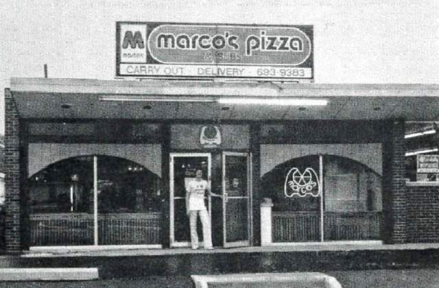 In a vintage black-and-white photo, a man holds open the door to a Marco's Pizza restaurant.