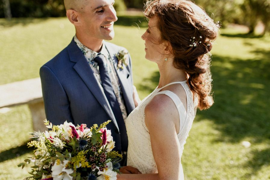 bride and groom smiling at each other under on a sunny day in Portugal
