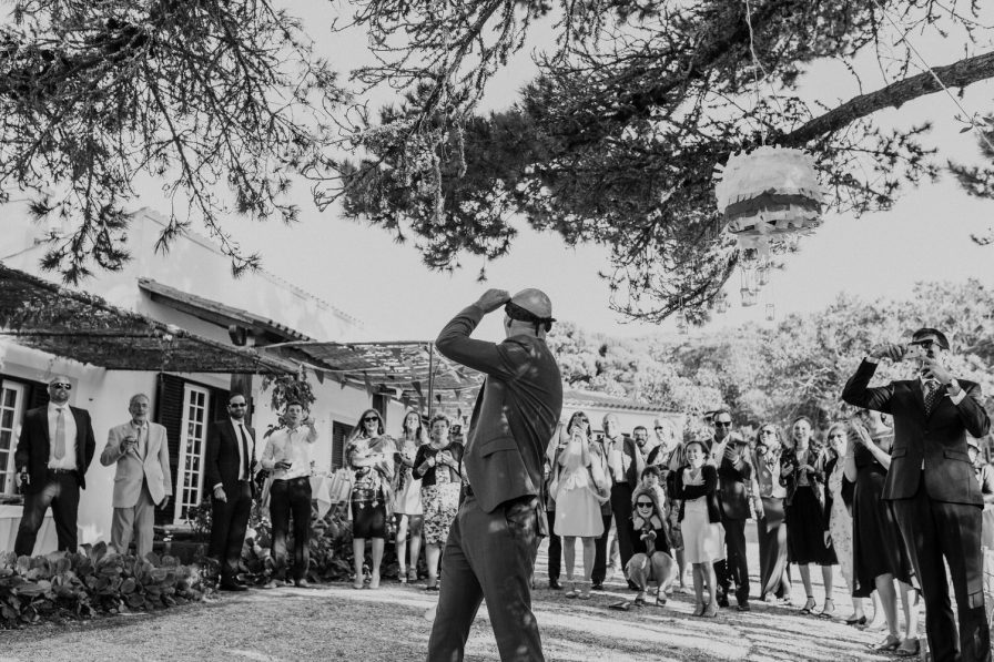 black and white photo of the groom looking at the wedding guests