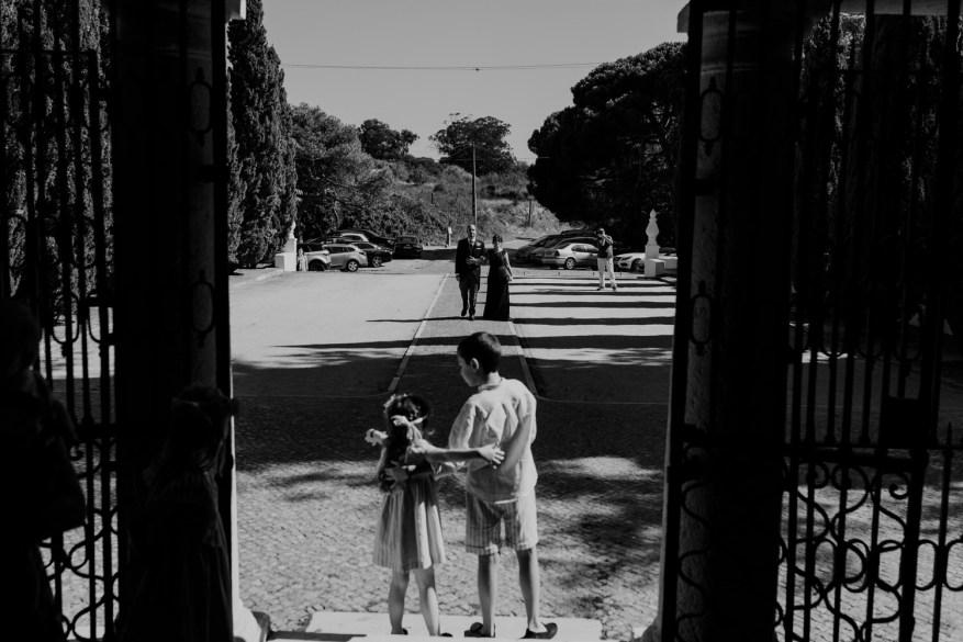 noivo caminha com a mãe para dentro no convento dos capuchos enquanto meninos das alianças esperam à porta