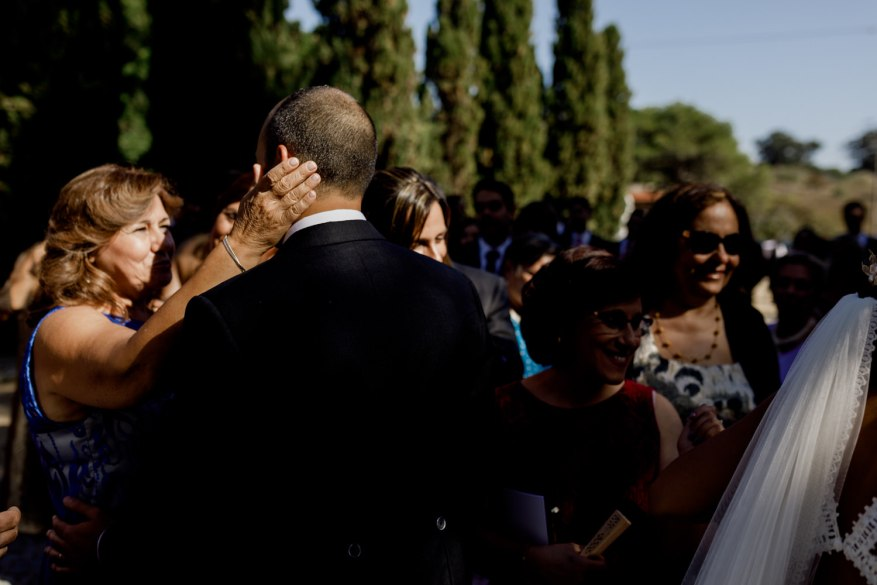 convidada acaricia a cara do noivo após cerimónia religiosa