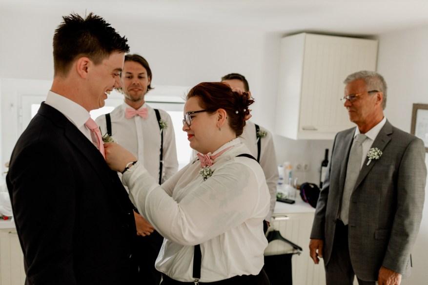 dama de honor ajuda o noivo a preparar-se
