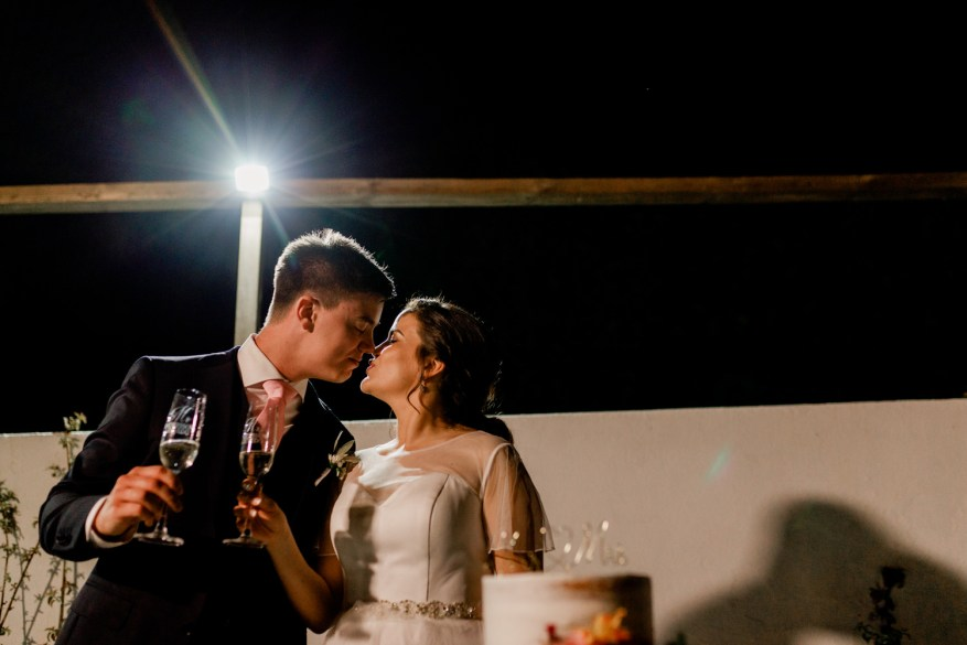 bride and groom kiss after drinking champagne