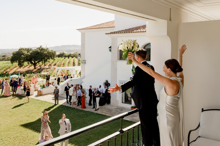 bride and groom cheer from the balcony