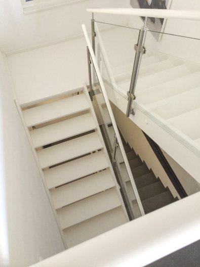 Weiß lackierte Treppe mit Podest und seitlich aufgesetztem Glasgeländer