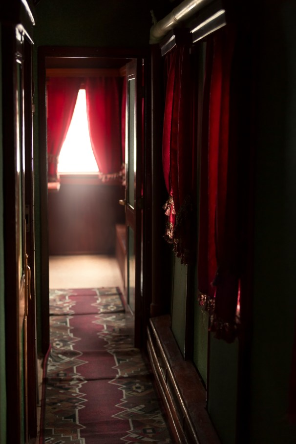 Interior of luxurious vintage train with hallway and red curtain