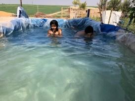 Mardin'de köy çocukları brandadan yapılan havuzda serinliyor