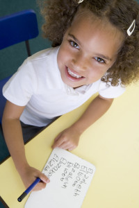 Girl learning to write name in primary class