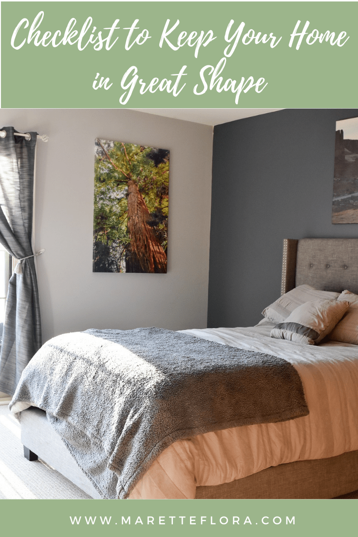 Checklist to keep your home in great shape: A master bedroom with a redwood tree canvas and gray curtains with gray bedding and a gray upholstered bedframe.